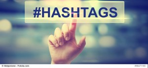 Hashtags concept with hand pressing a button on blurred abstract background